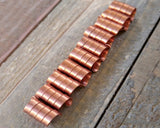 A line of Copper Dread Beads Set of 10 on a wooden background.