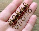 Set of 5 filigree beads held in hand to show scale.
