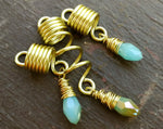 Light Blue, Gold Loc Beads, Set of 3 displayed on painted wood background.