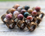 Set of 5 jasper dread beads on white washed wood background.