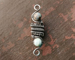 Silver, Terra Agate Dread Bead displayed on painted wood. Oxidized Finish.