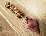 Red Jasper Arrowhead Dreadlock Bead on a wood background.