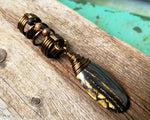 Tiger Iron Dreadlock Bead on a wood background.