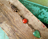 Chrysoprase, Red Jasper Copper Dread Bead on a wood background.