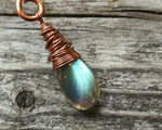 Woven Labradorite Dreadlock Bead on wood background. Closeup on labradorite.