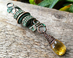 Woven Copper Patina and Citrine Dread Bead on Wood Background.