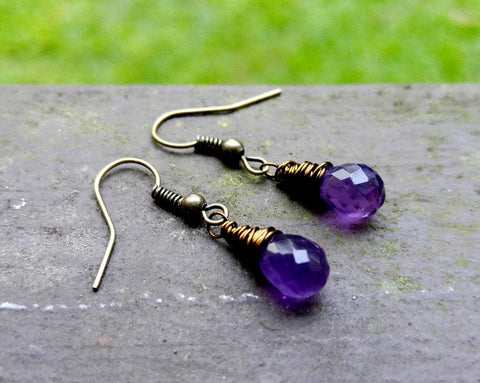Amethyst drop earrings displayed on painted wood