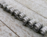 A side view of Oxidized Aluminum Dread Beads Set of 10 in a row.