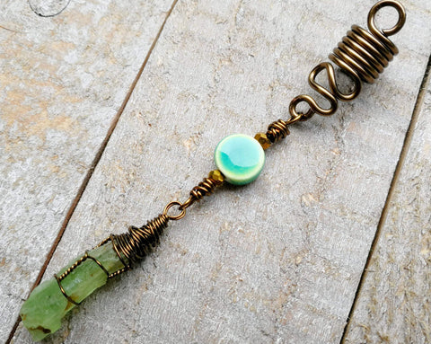 A close up view of a Green Kyanite Squiggle Loc Bead on a wooden background.