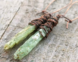 A side view of Green Kyanite Earrings wrapped in Oxidized Copper.