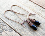 A pair of Black Onyx Earrings on a wooden background.