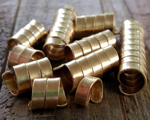A set of 10 Brass Dread Beads in varies of length on a wooden background.