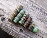 A back view of Patina Copper Dread Beads Set of 6 on a wooden background.