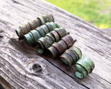 A side view of Patina Copper Dread Beads set of 6 in a row.