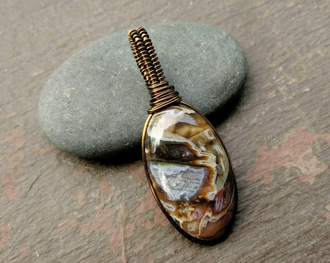 Agate pendant displayed against a rock