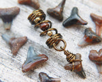 A close up view of a Shark Tooth Dread Bead with Wood Accents.