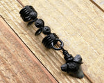 A close up view of a Shark Tooth Dread Bead with Black Lava Beads.