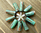 A top view of Green Patina Copper Tube Beads on a wooden background.