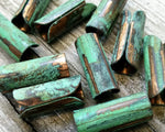 A close up view of Green Patina Copper Tube Beads.