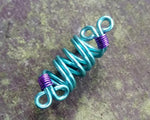 A top view of a Teal/Purple Dread Bead.