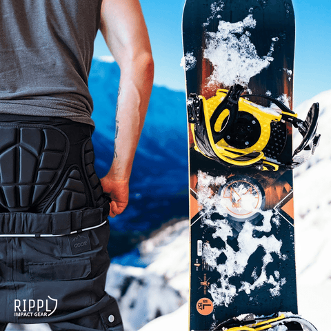 Snowboarder with impact shorts on standing next to snowboard with Snowy mountain backdrop