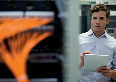 Picture of a man looking at a network rack