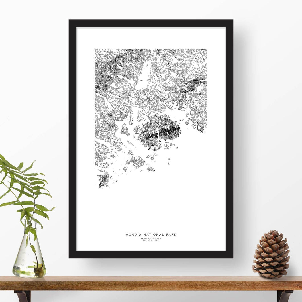 National park print of Acadia with black and white topography in a black 24x36 vertical frame.