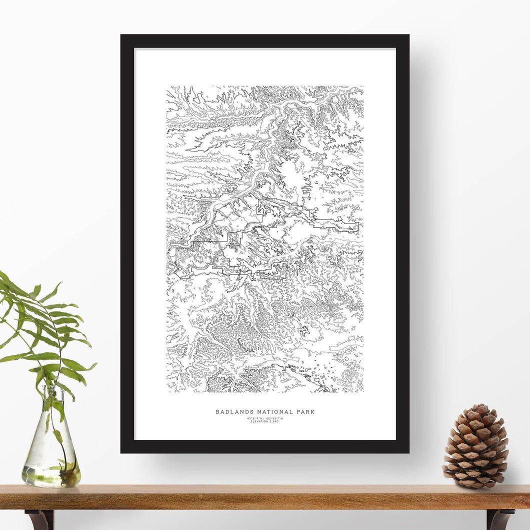 National park print of Badlands National Park with black and white topography in a black 24x36 vertical frame.