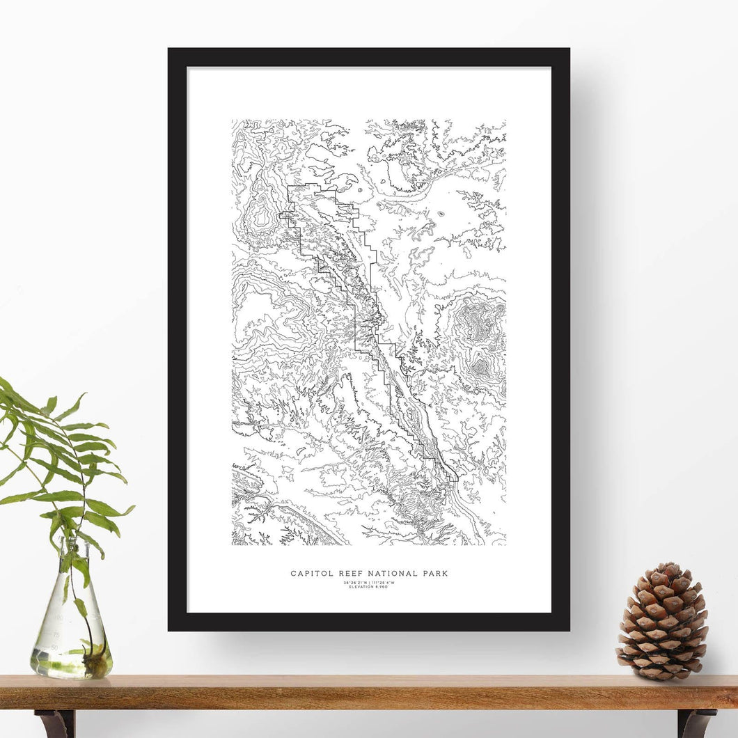National park print of Capitol Reef with black and white topography in a black 24x36 vertical frame.
