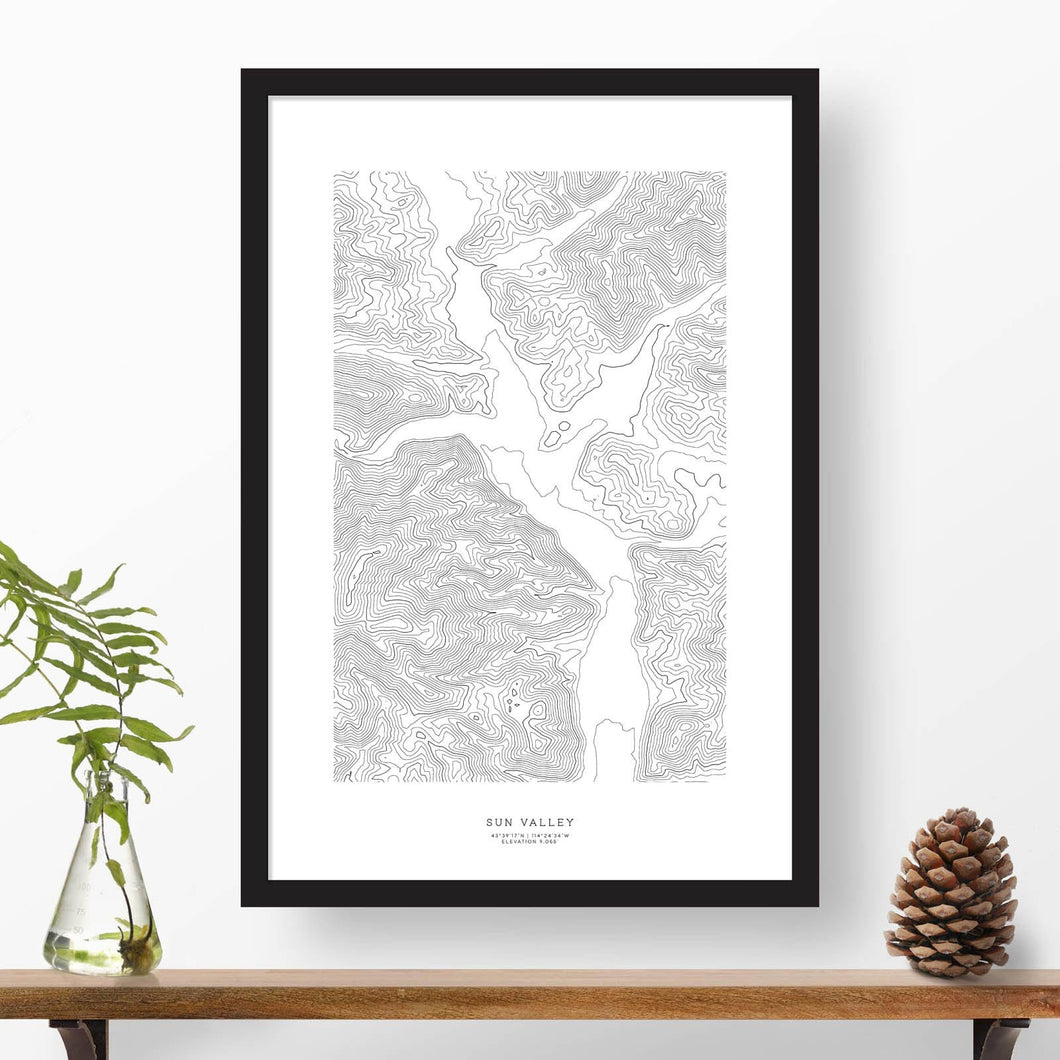 Black and white map and travel art of Sun Valley, Idaho. Topography contours are in black on a white background. Text below the image can be personalized for a perfect custom ski map art gift idea.