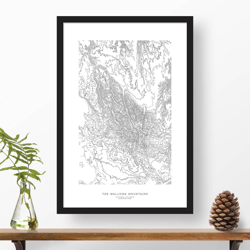 Black and white map and travel art of the Wallowa Mountains (the Wallowas). Topography contours are in black on a white background. Text below the image can be personalized for a perfect custom map art gift idea.