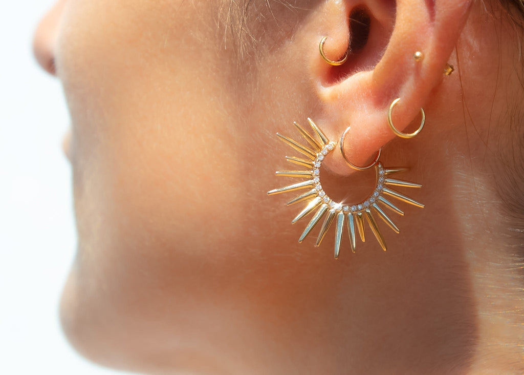 model wearing spiky 14k gold earrings with pave set diamonds