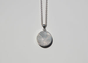back of silver pendant with wavy imprint
