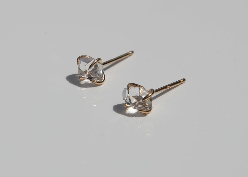 14k gold claw set clear Herkimer diamond stud earrings with sun shining through