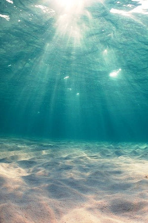 clear turquoise ocean water with sunlight rays