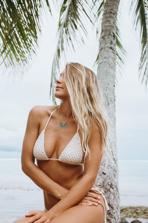seafoam blue urchin inspired necklace on blonde model in white crocheted bikini in front of palm tree