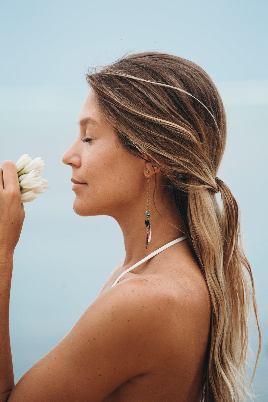 model smelling white flowers and wearing dangly earrings with freshwater pearls, fossilized shark teeth, shells, pink coral, and turquoise