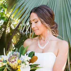 island bride with white fitted dress and white shell jewelry