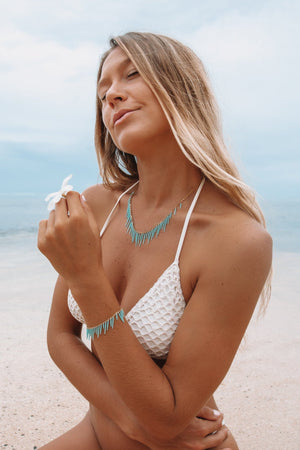 tan blonde model wearing white crocheted bikini wearing seafoam blue sea urchin fringe necklace and holding white plumeria flower