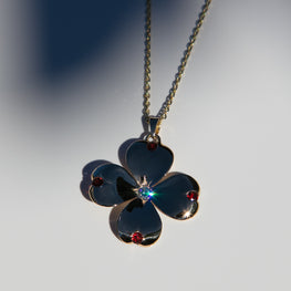 14k gold dogwood flower pendant with diamond in center and four garnet stones at the ends of petals