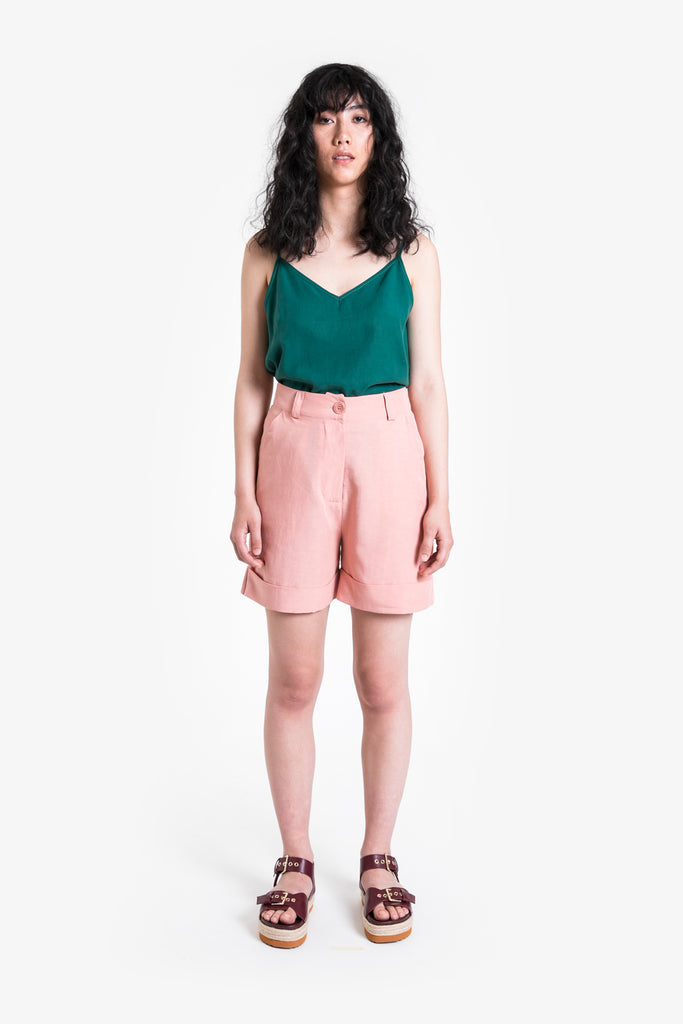 A pink mid-length short with belt keepers and folded cuff in a linen blend