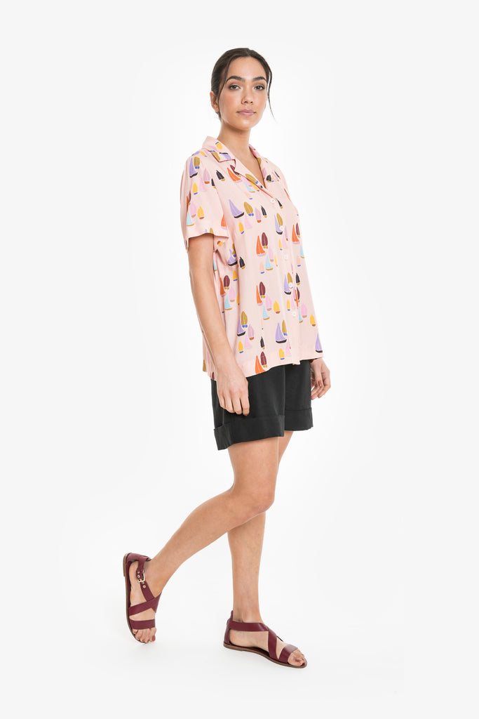 A bowling-style short sleeve shirt with open collar in a signature Obus sailboat print in peach