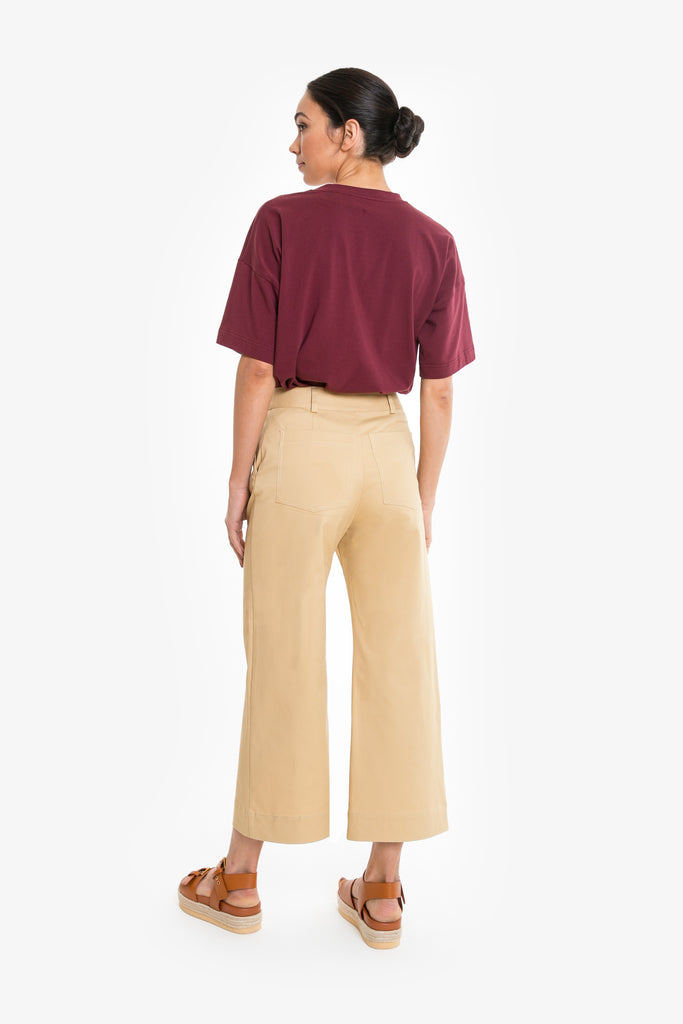 A wide leg cropped pant that sits high on the waist, made from cotton drill with gold zip and button