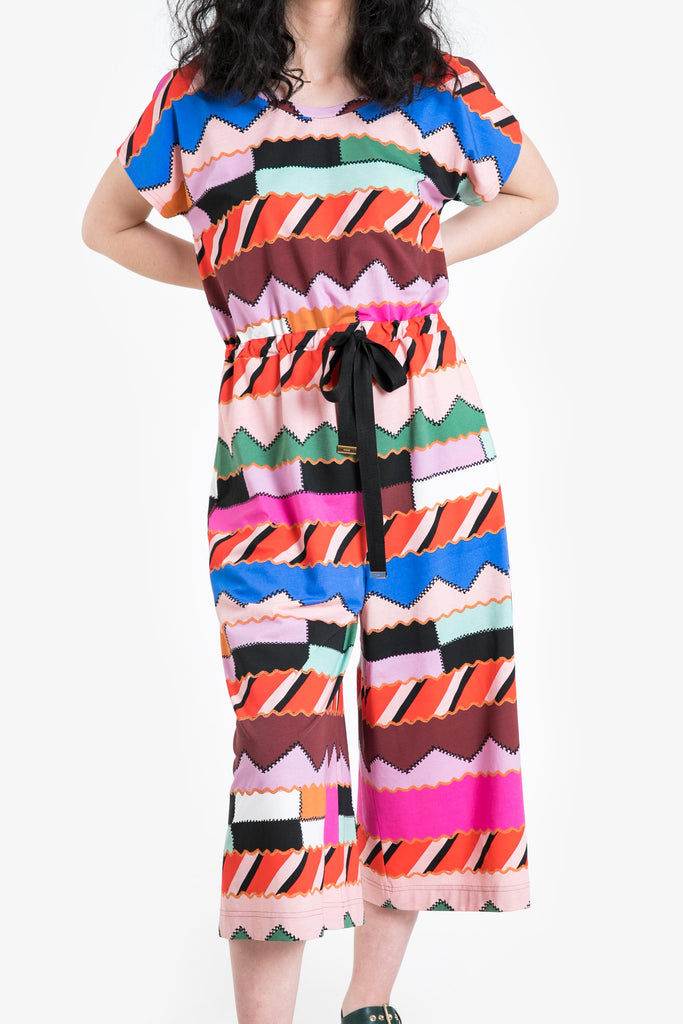 A wide legged, cropped jumpsuit with an elastic waist in a bold geometric pattern