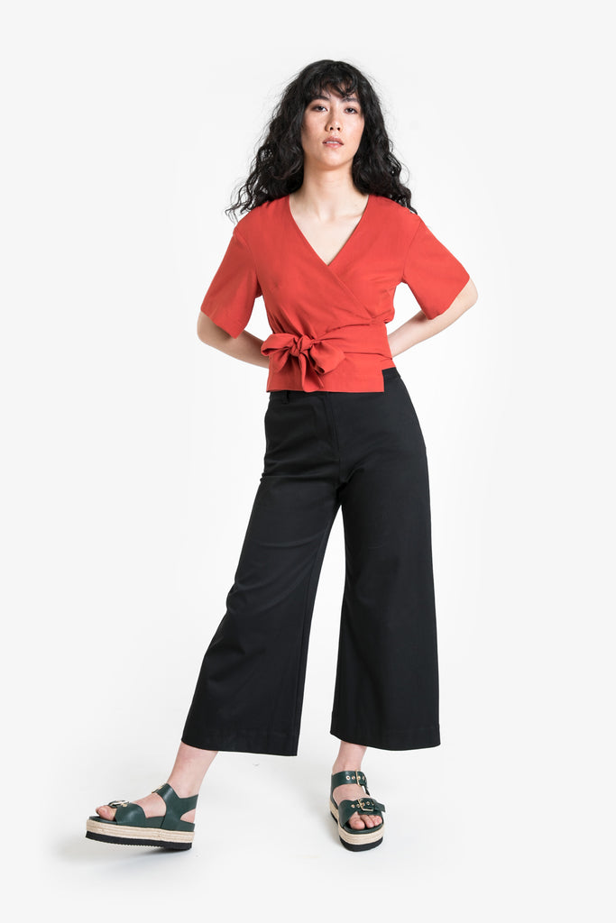 A wrap top with bow tie and elbow length sleeves in a red tencel/linen blend