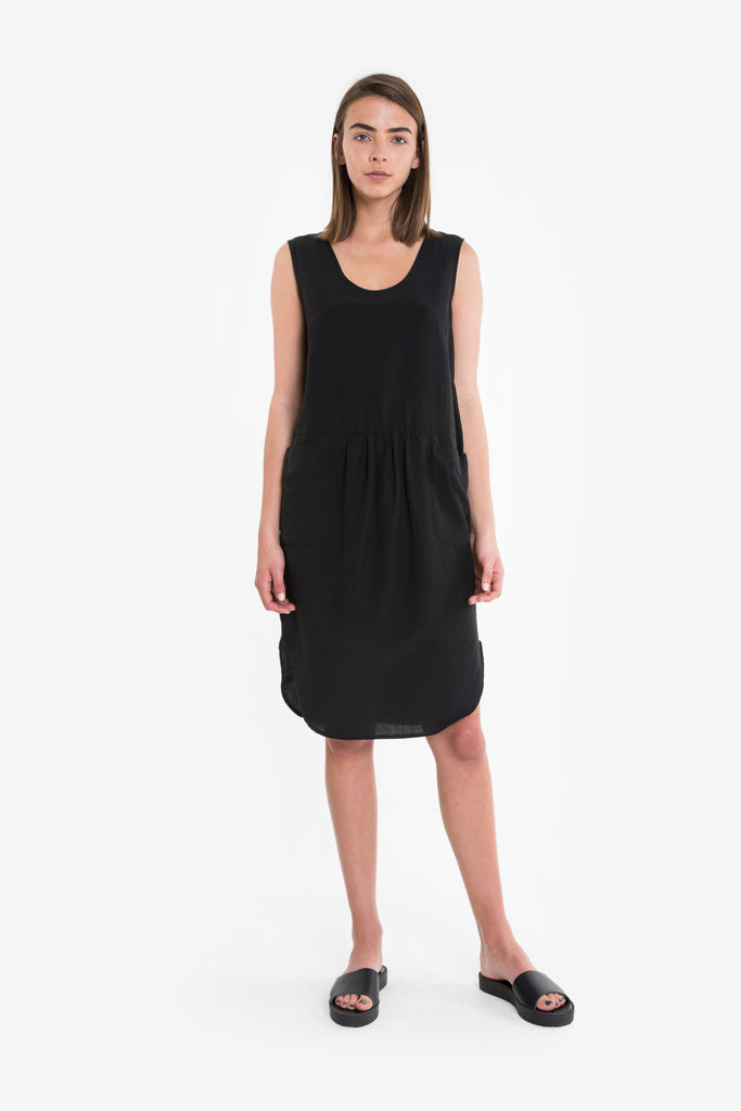 A black summer dress with a simple, casual cut and curved hemline, in linen