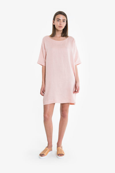 A short boxy, button-back dress featuring drop sleeves and a scoop neck, with buttons down the back