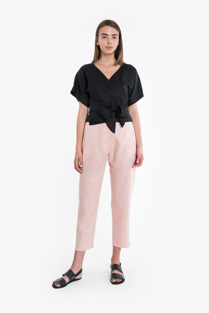 A black pink crossover wrap top with a tie at the hip.