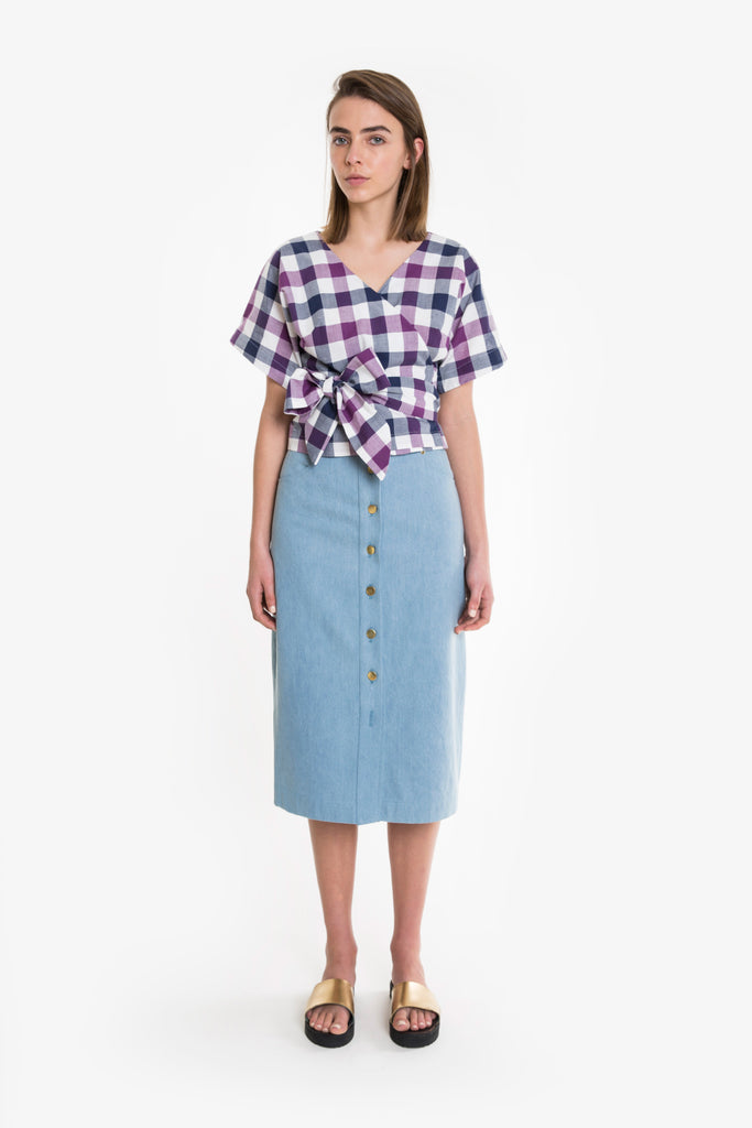 A check crossover wrap top with bow tie at the waist.