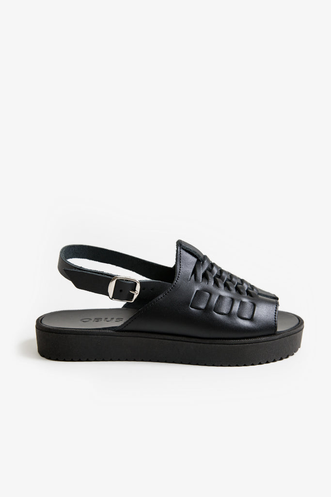 Black leather sandal with a woven top and platform sole